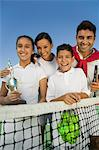 Tennis Family at net on tennis court, daughter holding trophy, portrait Stock Photo - Premium Royalty-Free, Artist: Blend Images, Code: 693-06013835