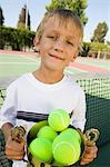 Boy on tennis court Holding Trophy Filled with tennis Balls, portrait Stock Photo - Premium Royalty-Free, Artist: Blend Images, Code: 693-06013889