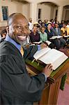 Preacher at altar with Bible preaching to Congregation, portrait Stock Photo - Premium Royalty-Free, Artist: Blend Images, Code: 693-06013979