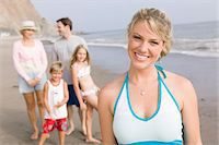 preteen bikini - Portrait of woman on beach with family Stock Photo - Premium Royalty-Freenull, Code: 693-06014106