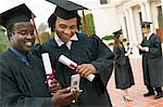 Two graduates Using Cell Phone outside Stock Photo - Premium Royalty-Free, Artist: Ikon Images, Code: 693-06014147