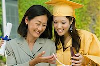Graduate and mother admiring necklace gift outside Stock Photo - Premium Royalty-Freenull, Code: 693-06014165
