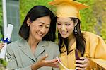 Graduate and mother admiring necklace gift outside Stock Photo - Premium Royalty-Free, Artist: Blend Images, Code: 693-06014165