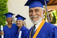 Senior graduate smiling outside with others behind, portrait Stock Photo - Premium Royalty-Freenull, Code: 693-06014217