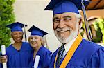 Senior graduate smiling outside with others behind, portrait Stock Photo - Premium Royalty-Free, Artist: Blend Images, Code: 693-06014217