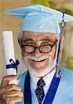 Senior graduate holding diploma outside, portrait Stock Photo - Premium Royalty-Freenull, Code: 693-06014223