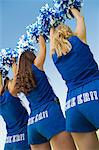 Three Cheerleaders rising pom-poms, rear view Stock Photo - Premium Royalty-Free, Artist: GreatStock, Code: 693-06014235