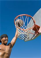 Young man dunking basketball into hoop Stock Photo - Premium Royalty-Freenull, Code: 693-06014249