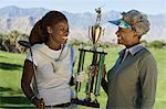Grandmother and granddaughter holding golf trophy, smiling Stock Photo - Premium Royalty-Free, Artist: CulturaRM, Code: 693-06014277