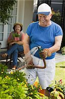 Senior man watering plants in garden, wife in background Stock Photo - Premium Royalty-Freenull, Code: 693-06014360
