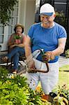 Senior man watering plants in garden, wife in background Stock Photo - Premium Royalty-Free, Artist: Blend Images, Code: 693-06014360
