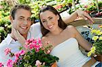 Young couple sitting on bench in garden centre, (portrait) Stock Photo - Premium Royalty-Free, Artist: Westend61, Code: 693-06014519