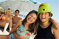 preteen girl swimsuit - Brother and sister sitting on beach, arm around, boy with bucket on head Stock Photo - Premium Royalty-Freenull, Code: