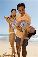 Parents carrying daughter (7-9) on beach Stock Photo - Premium Royalty-Freenull, Code: 693-06014721