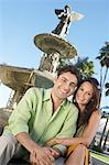 Smiling Couple, arms around, sitting in Front of Fountain Stock Photo - Premium Royalty-Free, Artist: Westend61, Code: 693-06014771