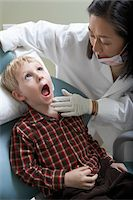 preteen open mouth - Female dentist examining boy (6-9) in surgery Stock Photo - Premium Royalty-Freenull, Code: 693-06014949