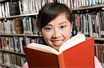 Young woman reading at library Stock Photo - Premium Royalty-Free, Artist: Blend Images, Code: 693-06014975