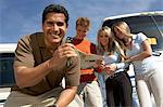 Man with keys to RV, customers in background, portrait Stock Photo - Premium Royalty-Free, Artist: Ikon Images, Code: 693-06015057