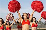 Cheerleaders with pom poms raised