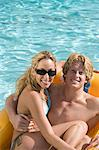 Portrait of Young Couple on Inflatable Raft in Pool Stock Photo - Premium Royalty-Free, Artist: Science Faction, Code: 693-06015338