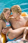 Portrait of Young Couple on Inflatable Raft in Pool Stock Photo - Premium Royalty-Free, Artist: Cultura RM, Code: 693-06015339