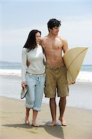 Young couple with surfboard on beach Stock Photo - Premium Royalty-Freenull, Code: 693-06015479