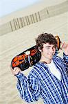 Young man with skateboard on shoulders on beach Stock Photo - Premium Royalty-Free, Artist: Cultura RM, Code: 693-06015509