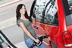 Young woman filling car with gas at gas station, elevated view Stock Photo - Premium Royalty-Free, Artist: Sarah Murray, Code: 693-06015512