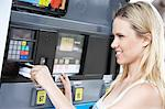Young woman paying with credit card at gas pump, head and shoulders Stock Photo - Premium Royalty-Free, Artist: Universal Images Group, Code: 693-06015516