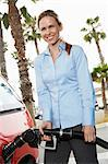 Young woman filling car at gas station Stock Photo - Premium Royalty-Free, Artist: Blend Images, Code: 693-06015519
