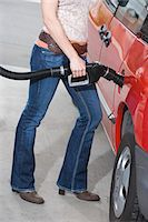 Woman by car with fuel pump Stock Photo - Premium Royalty-Freenull, Code: 693-06015527