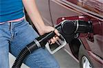 Woman by car with fuel pump, mid section Stock Photo - Premium Royalty-Free, Artist: Grant Harder, Code: 693-06015536