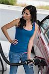 Woman by car with fuel pump Stock Photo - Premium Royalty-Free, Artist: Cultura RM, Code: 693-06015537