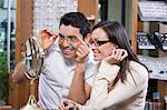 Man and woman trying on eyeglasses in store Stock Photo - Premium Royalty-Free, Artist: ableimages, Code: 693-06015815