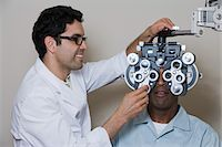 Optometrist examining patient's eyes Stock Photo - Premium Royalty-Freenull, Code: 693-06015871