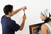 Couple hanging picture on interior wall, back view Stock Photo - Premium Royalty-Freenull, Code: 693-06016119