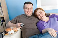 fat lady sitting - Overweight couple watching television on sofa Stock Photo - Premium Royalty-Freenull, Code: 693-06016368