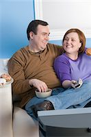 fat lady sitting - Overweight couple eating on sofa Stock Photo - Premium Royalty-Freenull, Code: 693-06016370