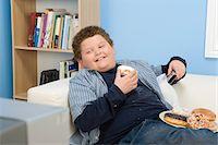 Boy Eating Donuts Stock Photo - Premium Royalty-Freenull, Code: 693-06016379