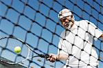 Senior man hitting tennis ball forehand near tennis net Stock Photo - Premium Royalty-Free, Artist: Aflo Sport, Code: 693-06016595