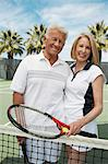Smiling Couple standing on Tennis Court, arms around, holding rackets Stock Photo - Premium Royalty-Free, Artist: Cultura RM, Code: 693-06016601