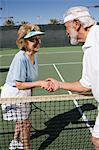 Two women shaking hands over tennis net Stock Photo - Premium Royalty-Free, Artist: Blend Images, Code: 693-06016649