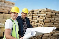supply - Construction Workers standing near supplies, wearing hard hats, looking at plan on Site Stock Photo - Premium Royalty-Freenull, Code: 693-06016692