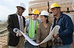 Two architects and two construction workers standing on construction site holding blueprints Stock Photo - Premium Royalty-Free, Artist: Andrew Kolb, Code: 693-06016827