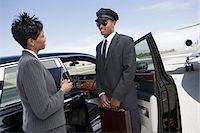 Mid-adult businesswoman and mid-adult chauffeur standing  in front of limousine and talking. Stock Photo - Premium Royalty-Freenull, Code: 693-06016970