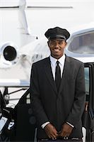 Portrait of mid-adult chauffeur standing in front of limousine and private jet. Stock Photo - Premium Royalty-Freenull, Code: 693-06017018