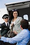 Mid-adult businesswoman getting out of airplane, two men assisting. Stock Photo - Premium Royalty-Free, Artist: Ikon Images, Code: 693-06017025