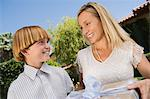 Boy giving birthday present to his mother Stock Photo - Premium Royalty-Free, Artist: Blend Images, Code: 693-06017240