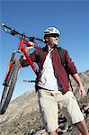 Young Man Carrying Mountain Bike in front of hills Stock Photo - Premium Royalty-Free, Artist: CulturaRM, Code: 693-06017513
