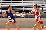 Female track athlete passing relay baton to another one Stock Photo - Premium Royalty-Free, Artist: Blend Images, Code: 693-06017865